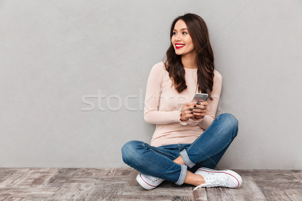 Portrait of smiling woman with red lips typing text message or s Stock photo © deandrobot