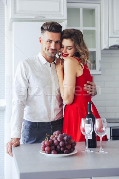 молодые человека обнять подруга красное платье глядя Сток-фото © deandrobot