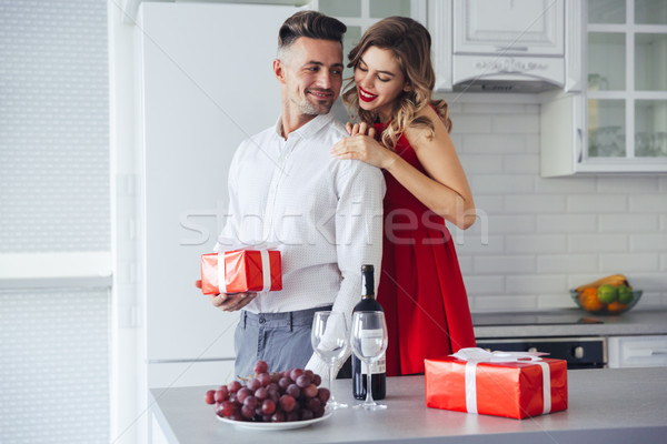 Young lady hug and looking at her man who holding present at home Stock photo © deandrobot