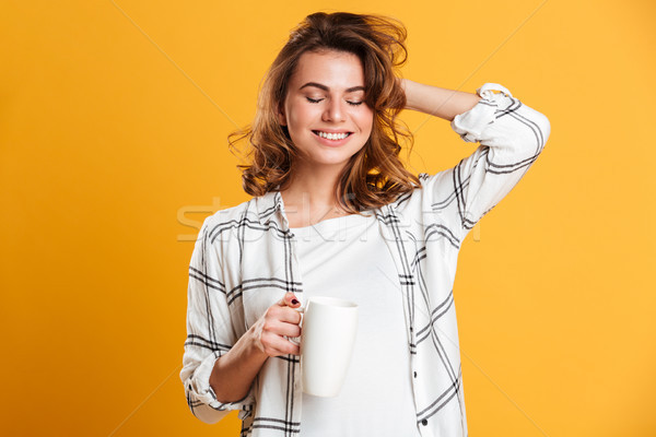 Beautiful young woman holding cup of tea. Eyes closed. Stock photo © deandrobot