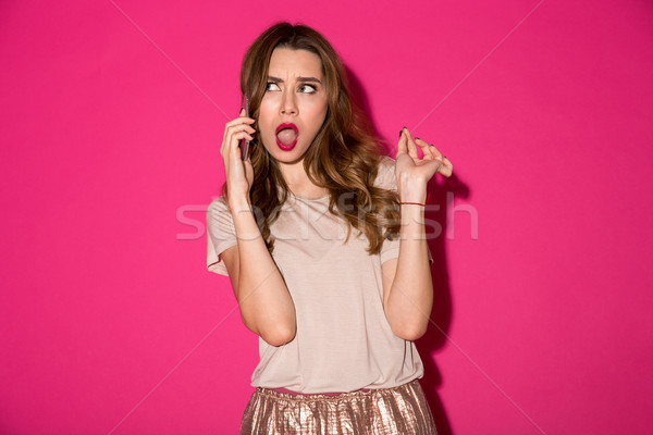 Displeased young woman talking by phone. Stock photo © deandrobot