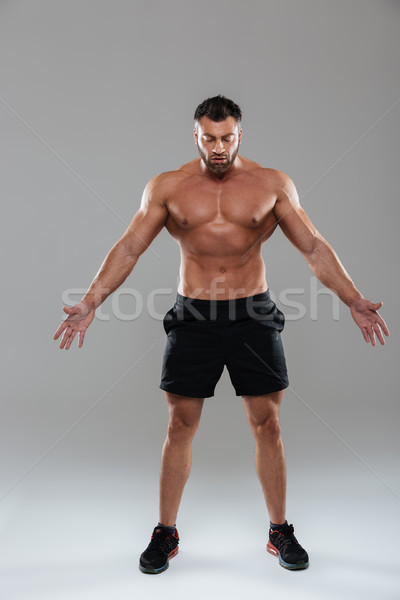 Full length portrait of a confident strong shirtless male bodybuilder Stock photo © deandrobot