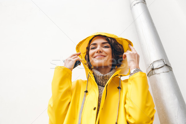 Pretty young woman with curly brown hair wearing yellow coat due Stock photo © deandrobot