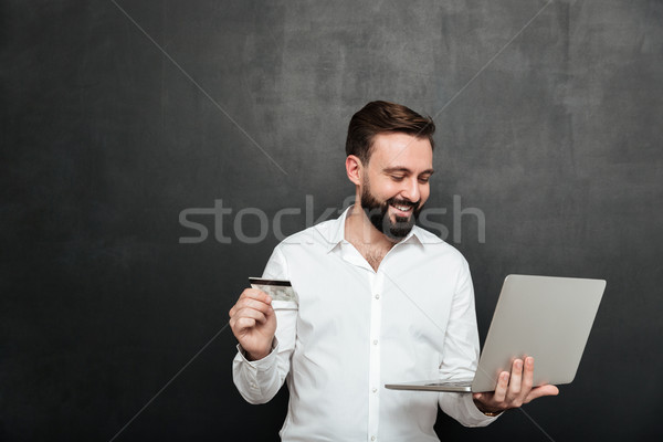 Portrait of cheerful man doing online payment in internet using  Stock photo © deandrobot
