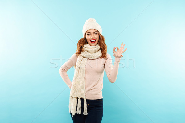 Cheerful caucasian lady in white scarf and hat showing ok gesture isolated Stock photo © deandrobot