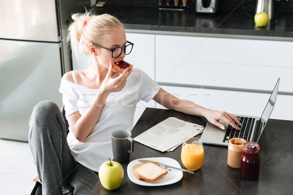 Young beautiful lady have breakfast and using laptop computer in kitchen Stock photo © deandrobot
