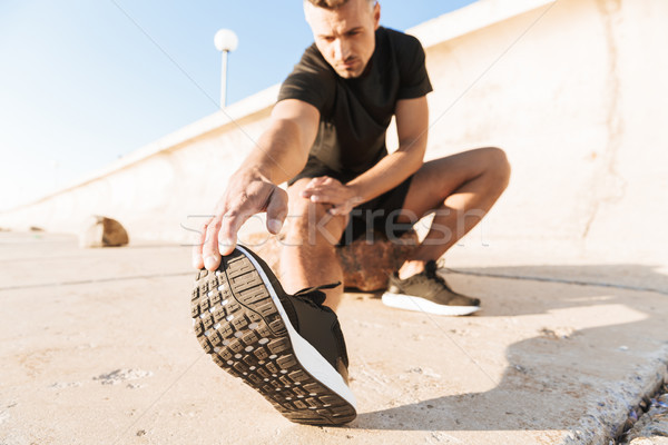 Portrait of a motivated sportsman doing stretching exercises Stock photo © deandrobot