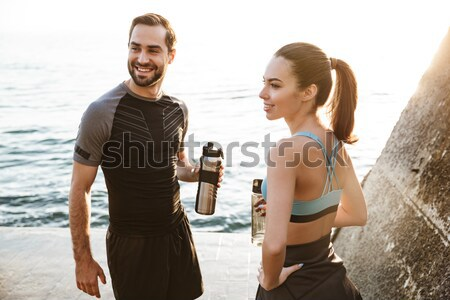 Joyful young sport couple looking at smartwatch Stock photo © deandrobot