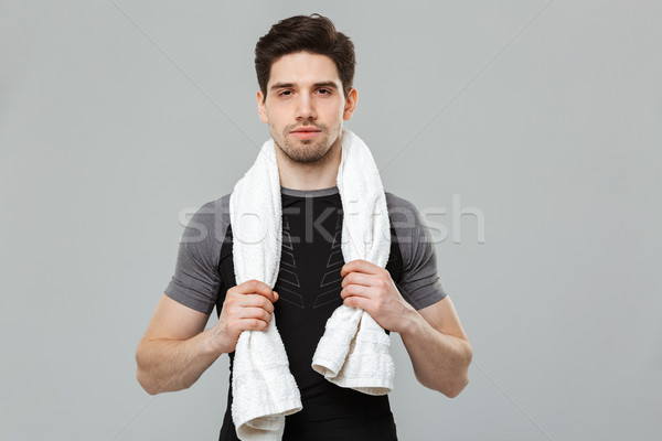 Handsome young sportsman holding towel. Stock photo © deandrobot