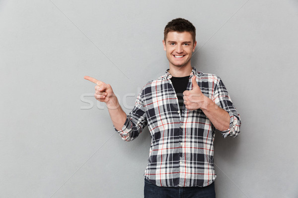 Portrait of a confident young man pointing fingers away Stock photo © deandrobot