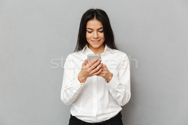 Photo of content young woman 30s in formal wear standing with sm Stock photo © deandrobot
