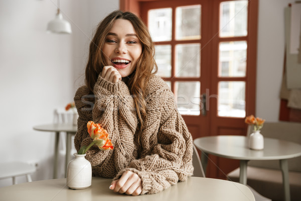 Photo of happy young woman in sweater sitting at table in cafe,  Stock photo © deandrobot