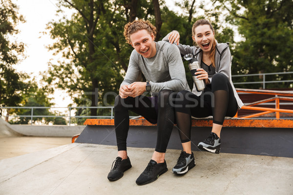 Image of attractive healthy couple guy and girl 20s in tracksuit Stock photo © deandrobot
