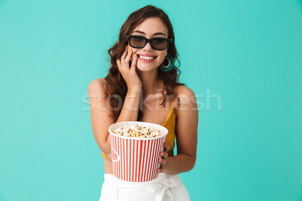 Photo of positive cute woman 20s wearing glasses holding bucket  Stock photo © deandrobot