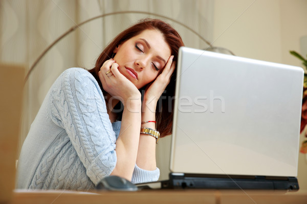 Tired woman with closing eyes sitting on her workout at home Stock photo © deandrobot
