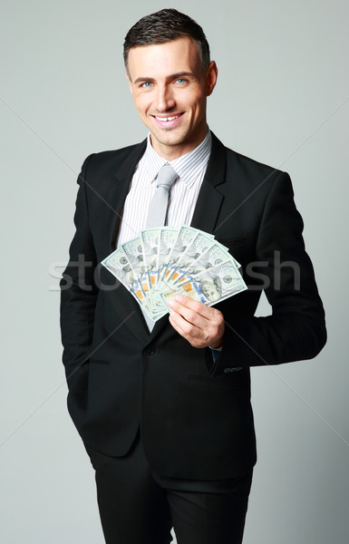 Happy businessman holding group of dollar bills on a gray background Stock photo © deandrobot