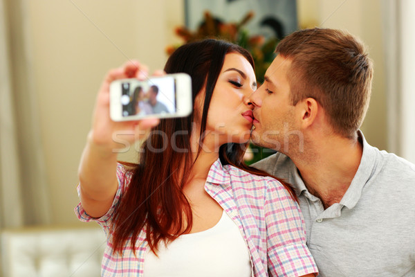Young couple kissing and making selfie photo on smarphone Stock photo © deandrobot