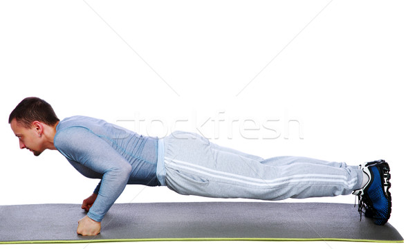 Fitness man doing push ups on mat over white background Stock photo © deandrobot