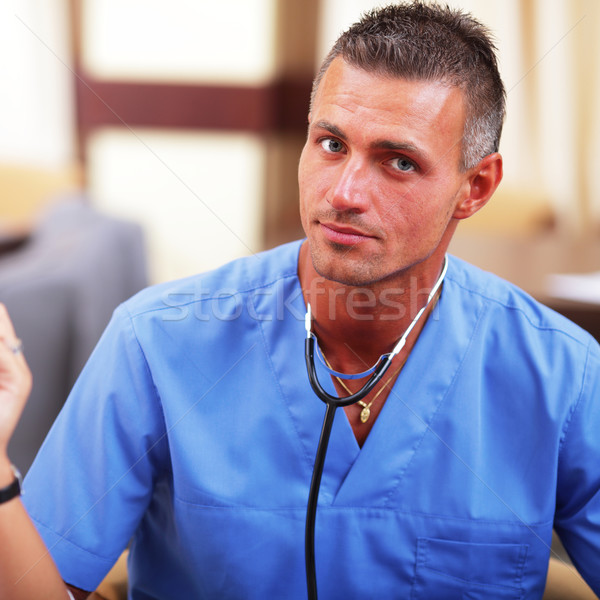 Portrait of a mature handsome doctor in blue scrubs with stethoscope Stock photo © deandrobot