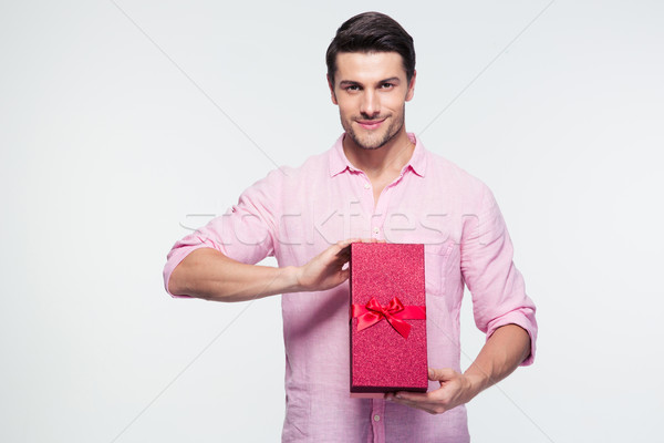 Happy young man holding gift box Stock photo © deandrobot