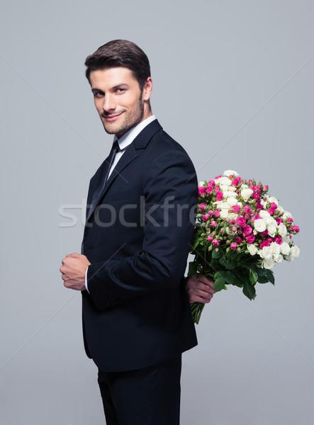 Businessman hiding bouquet of flowers behind his back Stock photo © deandrobot