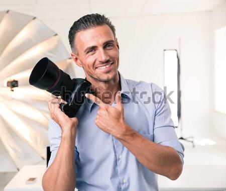 Stock photo: Handsome photographer holding camera