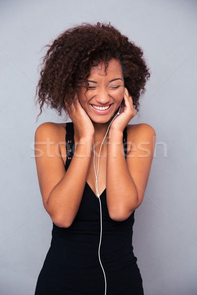 Afro american woman listening music in headphones Stock photo © deandrobot