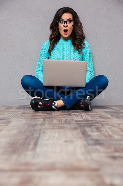 Surprised woman sitting on the floor with laptop Stock photo © deandrobot