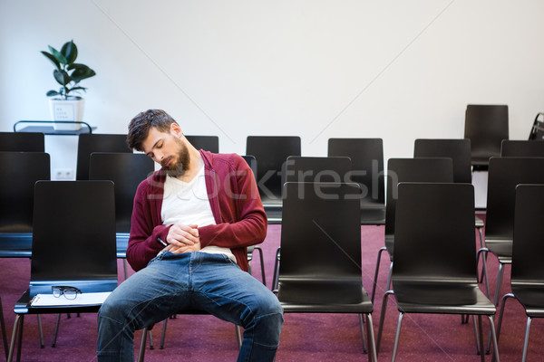 Bearded guy sitting and sleeping in conference room Stock photo © deandrobot