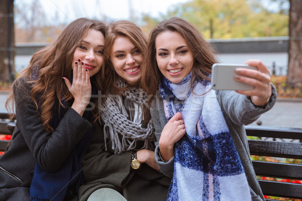 Three girlfriends making photo on smartphone Stock photo © deandrobot