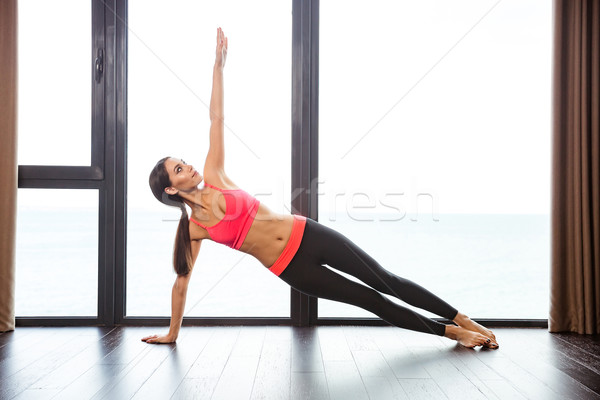 Woman doing yoga exercises in fitness gym Stock photo © deandrobot