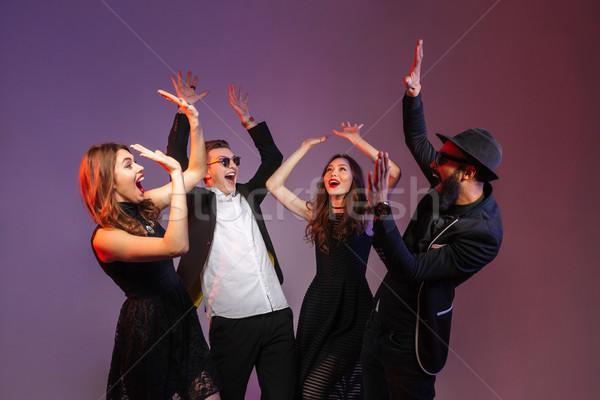Csoport boldog fiatalok áll együtt felemelt kezek Stock fotó © deandrobot