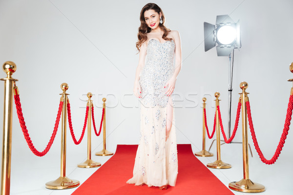Charming woman walking on red carpet  Stock photo © deandrobot