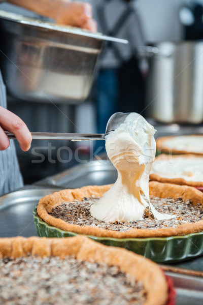 Chief cook in process of cooking several pies with cream Stock photo © deandrobot