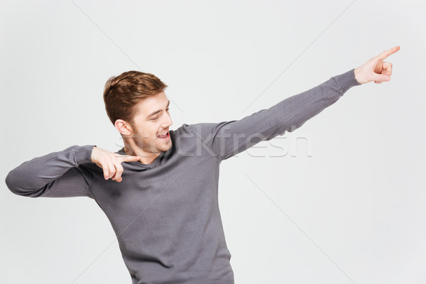 Happy handsome young man pointing away with both hands  Stock photo © deandrobot