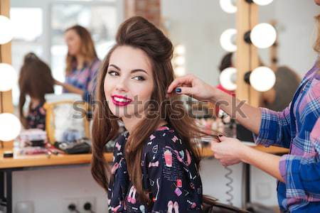 Hairdresser applying straightener for long hair of smiling  woman  Stock photo © deandrobot