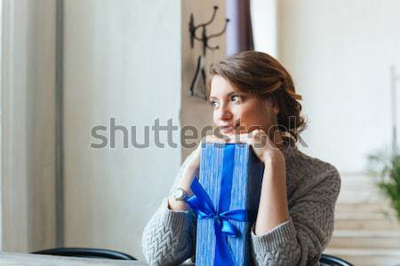 Woman sitting at the table with gift box Stock photo © deandrobot