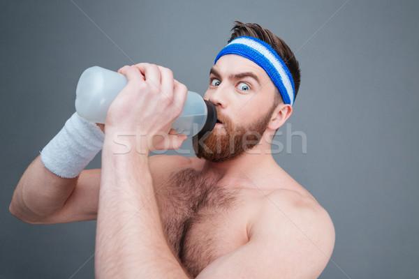 Portré meglepett szakállas sportoló ivóvíz szürke Stock fotó © deandrobot