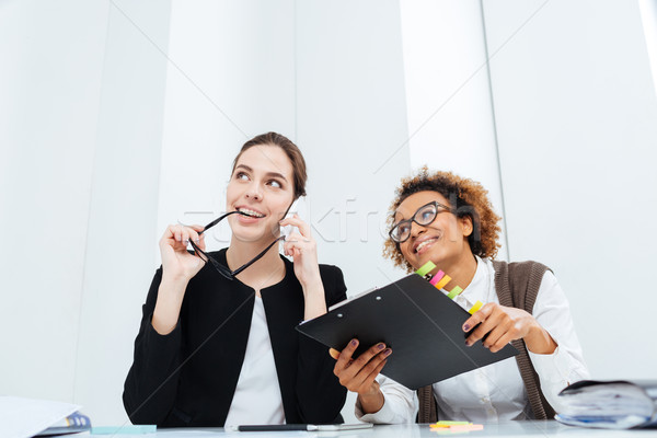 Stock photo: Two happy inspired businesswomen with clipboard dreaming and smiling