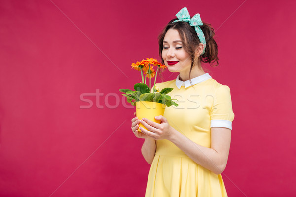 Happy pinup girl stamding and smelling orange flower in pot Stock photo © deandrobot