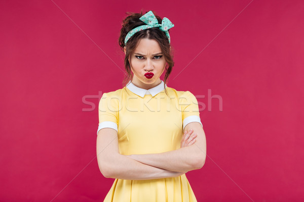 Sad frowning pinup girl standing with arms crossed Stock photo © deandrobot