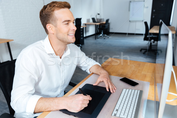 Happy male designer using computer and graphic tablet in office Stock photo © deandrobot