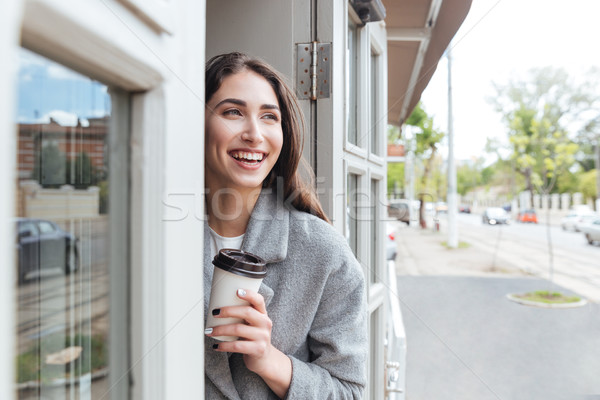 Happy cheerful smiling girl holding take away coffee Stock photo © deandrobot