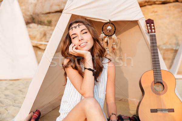 Beautiful brunette hippie girl sitting at tent with eyes closed Stock photo © deandrobot