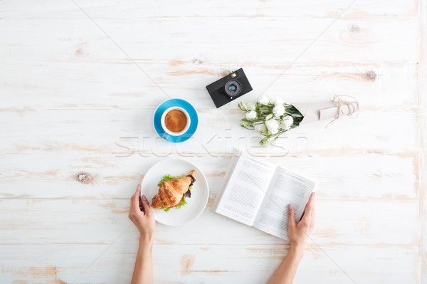 Hands of woman eating croissant with coffee and reading book Stock photo © deandrobot
