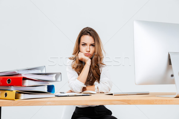 Upset sad businesswoman sitting at her working place Stock photo © deandrobot
