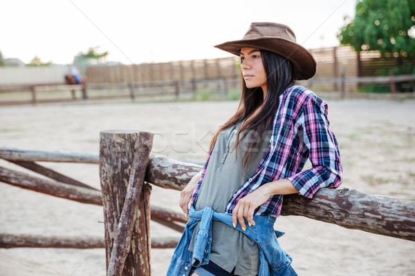 Woman cowgirl in hat and plaid shirt standing outdoors Stock photo © deandrobot
