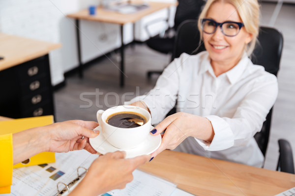Secretary bringing cup of coffee for her boss in office Stock photo © deandrobot