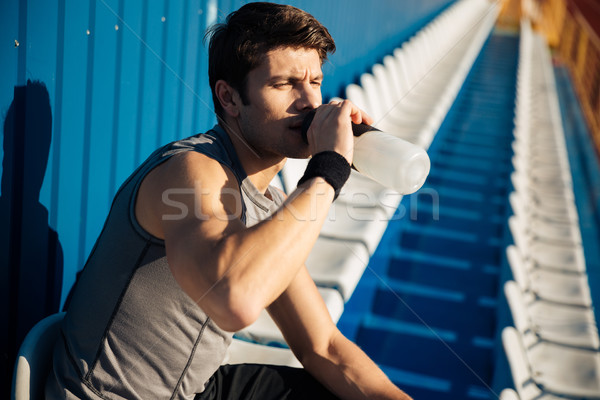Young handsome male athlete drinking water after workout Stock photo © deandrobot