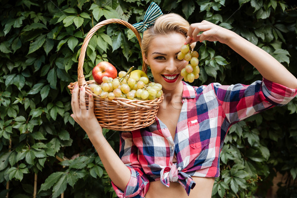 Pin-up girl with fruit basket covered eye by grape Stock photo © deandrobot